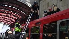 Police remove climate change activists who climbed on top of a train.