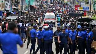 Sri Lankan police officers clear the road as an ambulance drives through carrying injured of Church blasts in Colombo