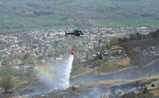 Firefighters use a helicopter to drop water as they tackle a large fire