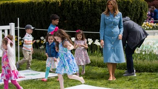 First lady Melania Trump watches children do hopscotch on the South Lawn of the White House in Washington.