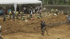 A mass funeral takes place for some of the 310 victims of the attacks.