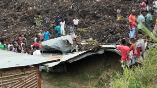 Locals and rescuers gather around a site where two houses were crushed by the collapse of a massive, sprawling dumpsite that hit just after midnight when rains poured in Pemba city on the northeastern coast of Mozambique.