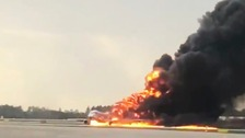 Flames billow from the plane at Moscow's Sheremetyevo airport.