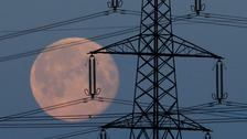 Full moon through electricity pylons