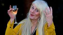 Picture of Melissa Ede lifting up a glass of champagne after winning £4 million on a scratchcard.