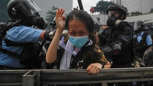 A protester holds her hands up as she tackled by riot police during a massive demonstration outside the Legislative Council in Hong Kong