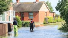 Two men walk through floodwater in Wainfleet in Lincolnshire.