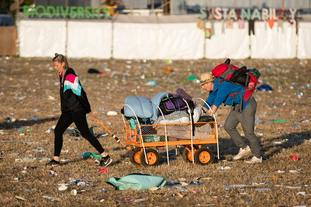 Music fans leave the Glastonbury site with their belongings.