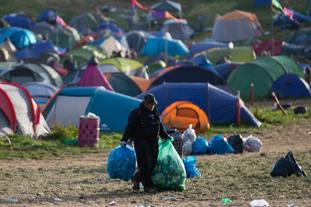 Workers set about collecting rubbish and discarded tents from the festival site.