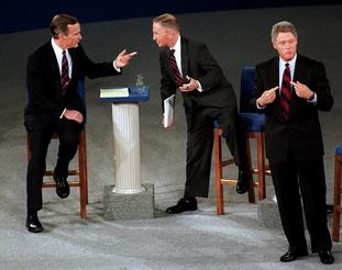 President George H.W. Bush, left, talks with independent candidate Ross Perot as Democratic candidate Bill Clinton stands aside at the end of their second presidential debate