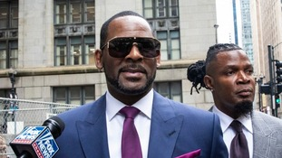 Musician R Kelly, centre, arriving for a court hearing.