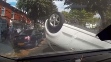 A white VW Polo is pictured lying on its roof