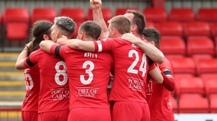 Larne players celebrate together during the game