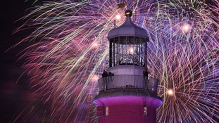 Fireworks light up the sky behind Smeaton's Tower on Plymouth Hoe.