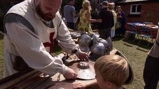 Man showing boy old armour and helmets from medieval period.