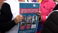 Woman holding poster calling for equal pay in Guernsey.