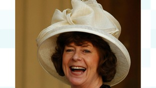 Pam Ayres wearing a white hat, holding her MBE in the grounds of Buckingham Palace.