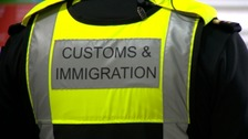 A hi-vis vest of a Customs and Immigration official