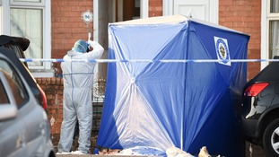 A forensic officer photographs the front of the house beside a forensic tent