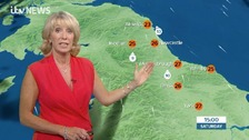 Emma in orange top in front of NE weather graphics
