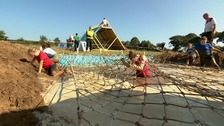 Kids taking part in a muddy run with netting and a muddy pool