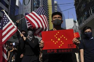 Protesters carry US flags and a placard reading You trust Communist party? as they march on a street in Hong Kong.