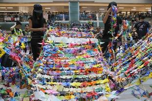 Protesters arranging origami cranes used in a display at an anti-government rally inside a shopping mall at the Sha Tin district
