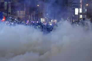 Tear gas fills the street as protesters continue to battle with police