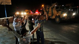 Local residents jeer and applaud as a convoy of Turkish forces vehicles and trucks carrying tanks and armoured personnel carriers is driven in Sanliurfa province, southeastern Turkey on Tuesday.