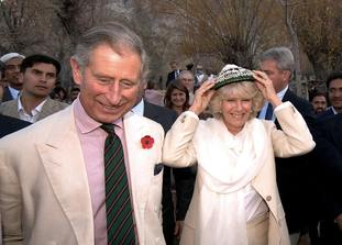 The Prince of Wales watches as the Duchess of Cornwall wears a hat given to her as a present from the villagers of Nansoq in northern Pakistan