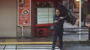A man battles with his umbrella as he crosses the road in Otemachi district of Tokyo