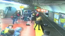 Woman saved after she is pushed onto tracks by fainting passenger