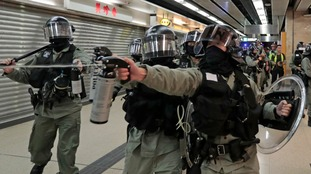 Riot police fire pepper spray toward people at a shopping mall in Hong Kong.