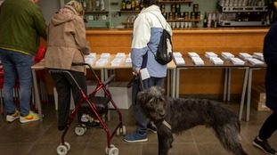 People pick their ballot papers to cast their vote for the general election in Barcelona, Spain.