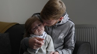 An image of Oscar Bedford being held by his dad at his home