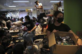 Protesters pass out goggles to fellow demonstrators at Hong Kong Polytechnic University