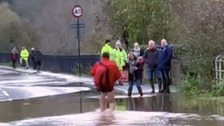 Postman strips off to his underwear to get through floods