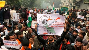 A protestor holds up a placard and sits with others in New Delhi