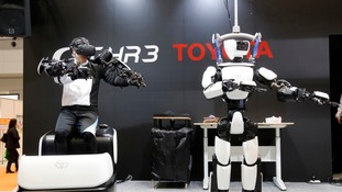 The T-HR3 robot, right, is remotely controlled by its staff member, left