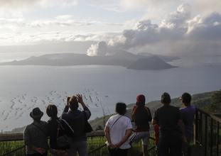 People look from Tagaytay, Cavite province, south of Manila, as Taal Volcano continues to spew ash