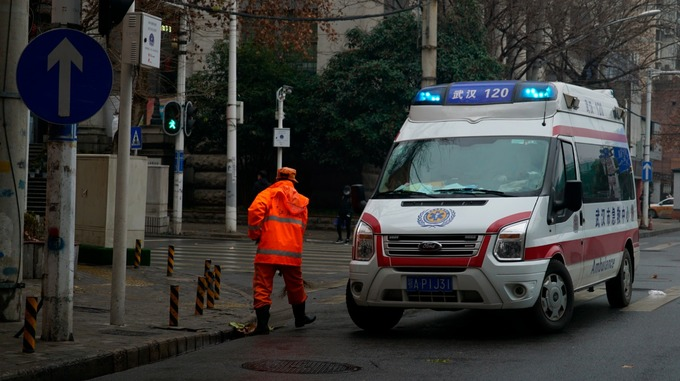 An ambulance drives by a street cleaner in Wuhan, China, as the number of people infected by the coronavirus reached more than 400.