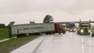 A large truck is blown off course by the tornado.