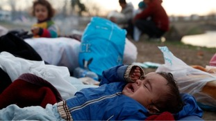 A baby cries as migrants gather next to a river in Edirne, Turkey, near Turkish-Greek border.