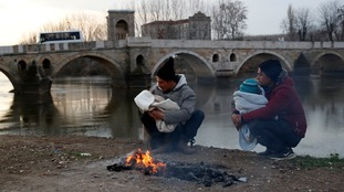 Migrants hold their babies as they try to warm themselves next to a river in Edirne near the Turkish-Greek border.