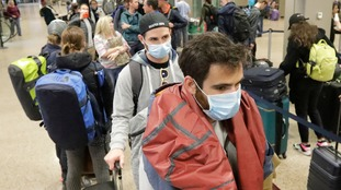 Masked passengers stand in line to collect luggage at an airport in Utah.