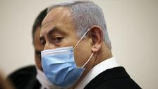 Israeli prime minister Benjamin Netanyahu wears a face mask as he stands inside the court room