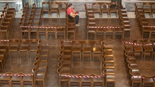 A woman sits on seats arranged for social distancing at Westminster Cathedral