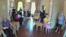 Residents of a care home sitting in their lounge joined by staff singing 'well meet again' as a tribute to Dame Vera Lynn.