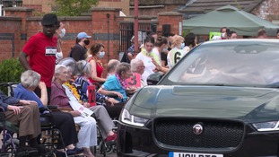 Someone waving from the window of a car towards care home residents seated outside