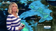 Emma Jesson in blue and white stripey top in front of Granada graphics
